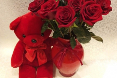 roses in glass vase with red teddy bear