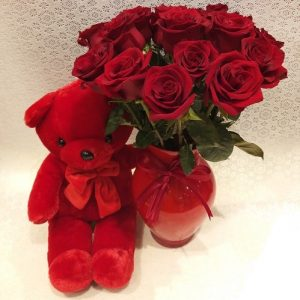 bunch of roses in glass vase with red teddy bear